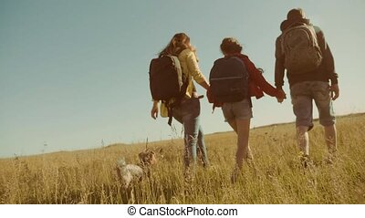 happy family slow motion video walking on nature boy girl and mom in a field on trekking trip. tourists with backpacks traveling. happy family lifestyle travel tourism concept