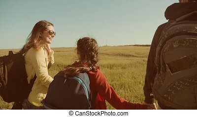 happy family slow motion video walking on nature boy girl and mom in a field on trekking trip. tourists with backpacks traveling. lifestyle happy family travel tourism concept