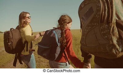 happy family slow motion video walking on nature boy girl and mom in a field on trekking trip. tourists with lifestyle backpacks traveling. happy family travel tourism concept