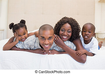 Happy family smiling at camera together on bed