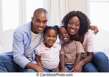 Happy family smiling at camera together at home in the...