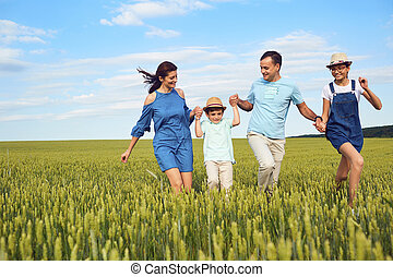 Happy family smiling running on the field in nature