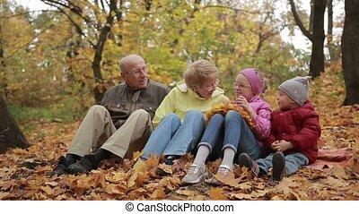 Happy family spending leisure in autumn park