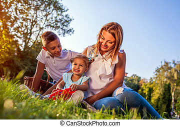 Happy family spending time outdoors sittting on grass in park. Mom with two children smiling. Family values