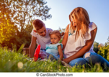 Happy family spending time outdoors sittting on grass in park. Mom with two children smiling. Mother's day