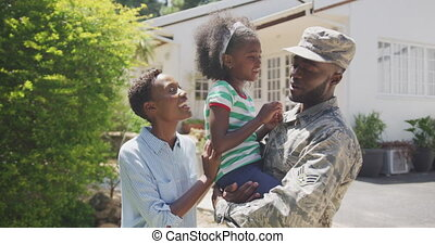 Side view of an African American family enjoying time in the garden, a man is wearing military uniform, holding up his daughter, looking at her, on a sunny day, in slow motion