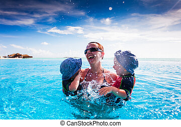 Happy family splashing in swimming pool on a tropical resort