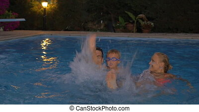 Happy family splashing water in the pool