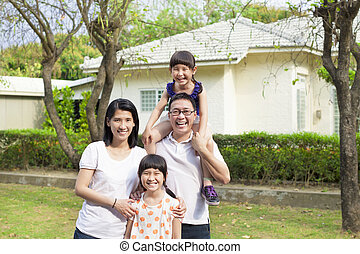 Happy family standing before their house