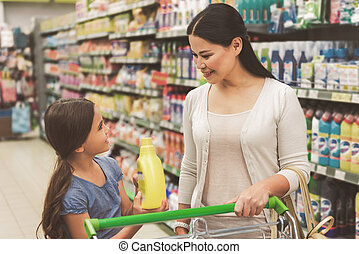 Happy family standing in supermarket - Joyous smiling girl...