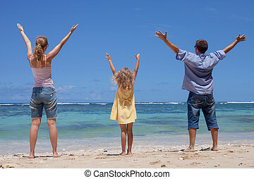 Happy family standing on the beach in the day time