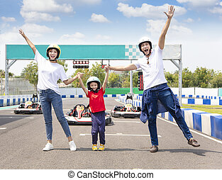 happy family standing on the go kart race track