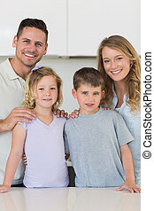 Happy family standing together in kitchen