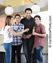 Happy Family Standing With Girl In Ice Cream Parlor