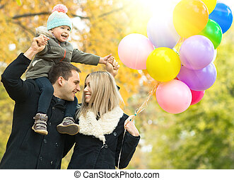 happy family with little child and air-balloons, outing in...