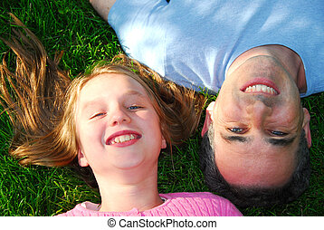 Happy family - Father and daughter lying on green grass and...