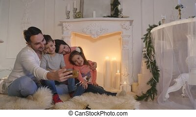 Happy family taking self portrait with smartphone during Christmas at home