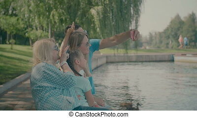Happy family taking selfie on smart phone by lake