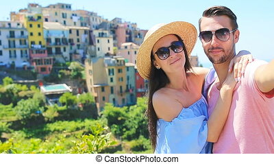 Happy family taking selfie with view of the old coastal town background of Corniglia, Cinque Terre national park, Liguria, Italy ,Europe