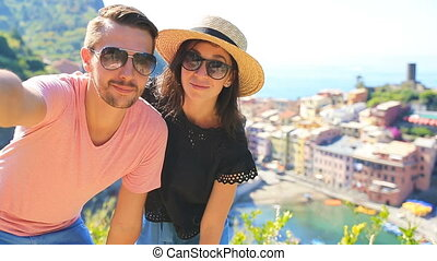 Happy family taking selfie with view of the old coastal town background of Vernazza, Cinque Terre national park, Liguria, Italy ,Europe