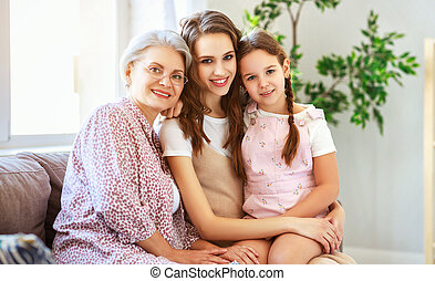 family three generations grandmother, mother and child play and laugh at home