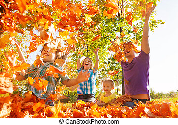 Happy family throwing leaves in air while sitting