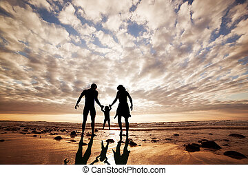 Happy family together hand in hand on the beach at sunset....