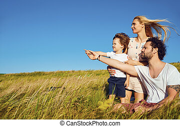 Happy family together in nature against the blue sky