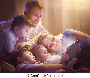 Happy family together watching movie on tablet computer in dark room