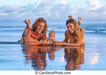 Happy family travel - father, mother, baby son on sunset beach