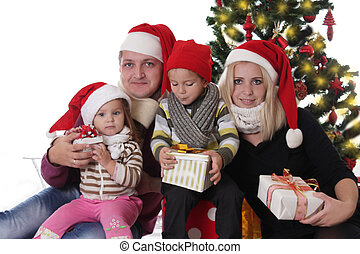 Happy family under Christmas tre opening presents