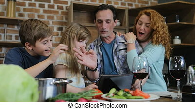 Happy Family Use Digital Tablet Touch Screen In Kitchen While Cooking Dinner Parents With Two Children At Home Talking