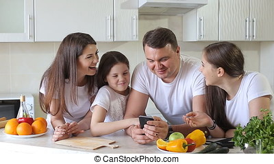 Happy Family Uses a Smartphone For Shopping on the Internet.