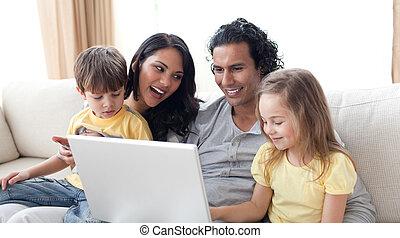 Happy family using laptop on sofa