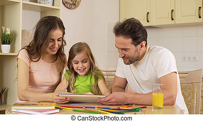 Happy family viewing photos on tablet, girl sliding pictures on touchscreen