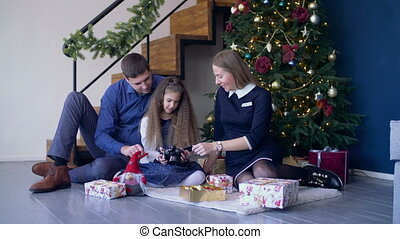 Happy family viewing pictures on camera at xmas - Joyful...