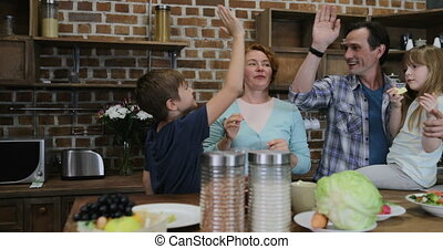 Happy Family Waiting For Preparing Food In Kitchen Cheerful Parents And Children Giving High Five After Cooking At Home Together