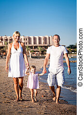 Happy family walking at the beach
