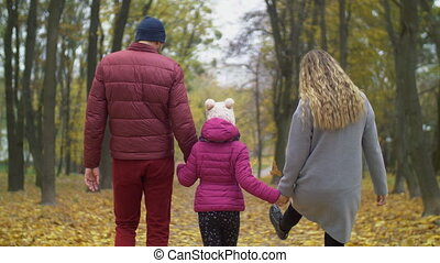 Happy family walking down road in autumn nature - Rear view...