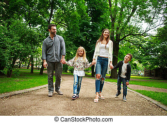 Happy family walking holding hands in green city park