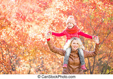 Happy family walking in fall or autumn park
