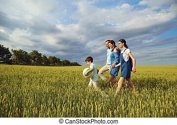 Happy family walking in summer field