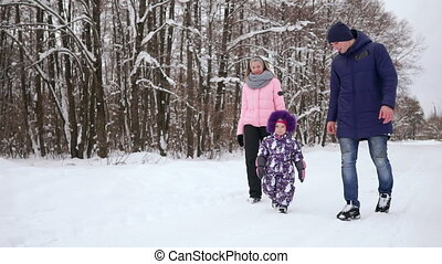 Happy family walking in winter park. A woman with a child on a snowy winter walk.