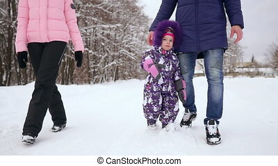 Happy family walking in winter park. A woman with a child on...