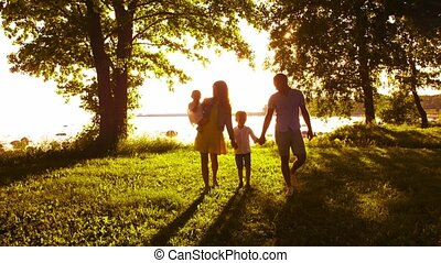 Happy family walking near the sea. Field and trees in...
