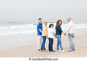 Happy family walking on beach
