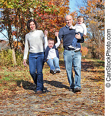 Happy family walking on path during autumn
