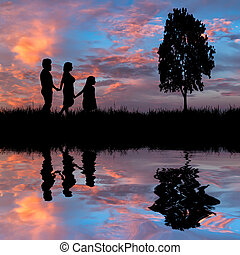 Happy family walking on the lake coast on a background of...