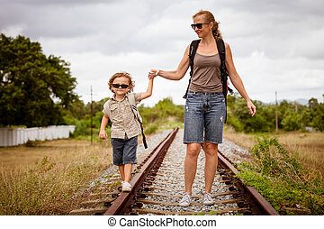 Happy family walking on the railway