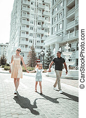 Happy family walking on their way to the downtown.